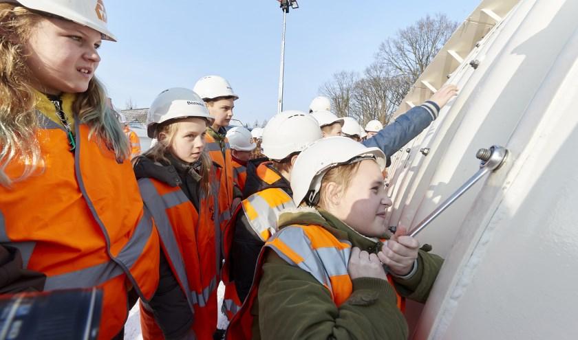 Leerlingen van basisschool De Blokkendoos draaien de laatste van de 12.000 bouten voor de nieuwe tunnel voor de snelfietsroute aan.