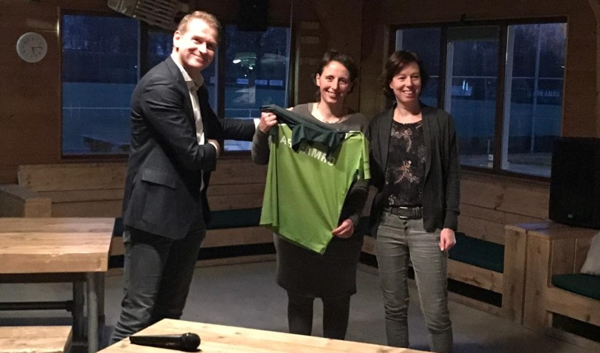 Voorzitter Gerard Breukelman van MHC Woerden reikt Marly Engel en Yvonne de Wit van Actie4Kids een hockeyshirt aan.