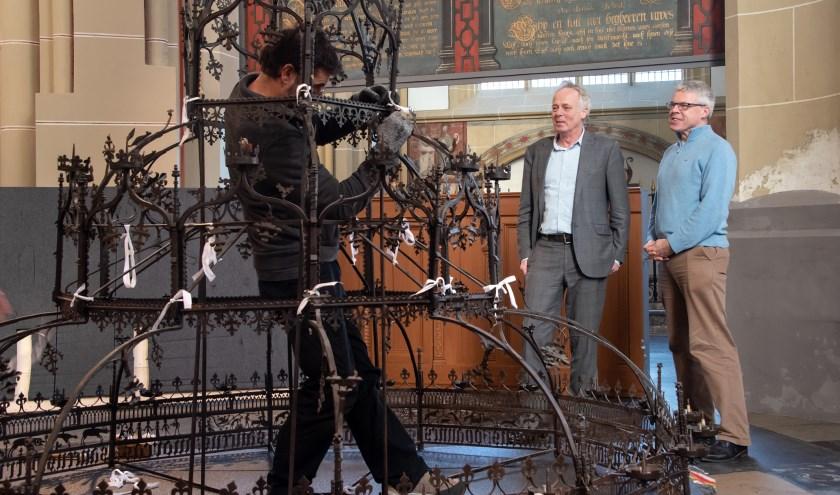 De kaarsenkroon wordt weer op zijn plek gebracht inder toeziend oog van Herman Krans (links) en Johan Oosterman. (Foto: Willem Feith)