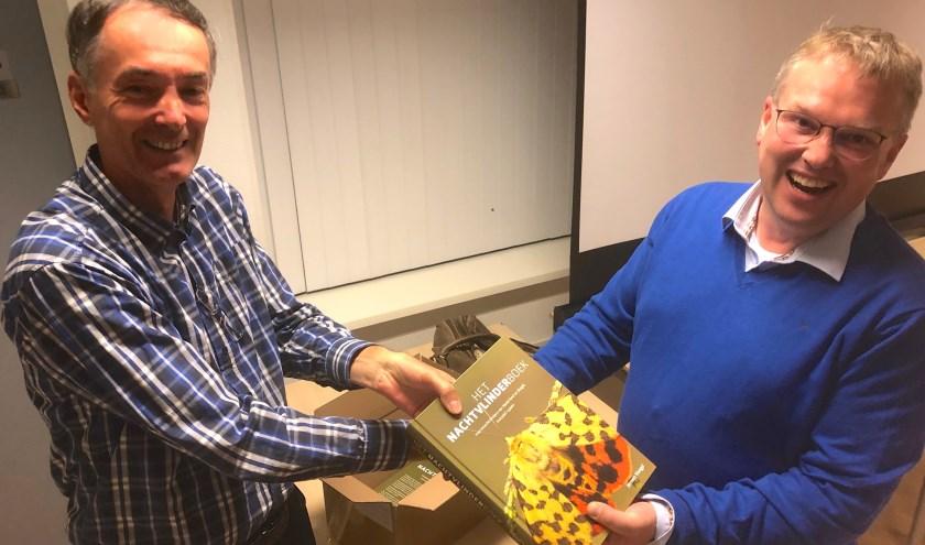Links de oud-voorzitter van de vogelwerkgroep Winfried van Meerendonk die graag een exemplaar van rechts Jeroen Voogd koopt. Op de cover de purperbeer. Foto: Simone Langeveld