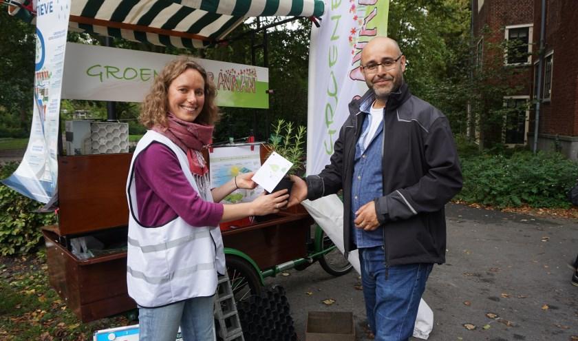 Nabil Feki krijgt een rozemarijnplant cadeau van Groene Karavaan-vrijwilliger Ina Schaafsma om te geven aan een buur.