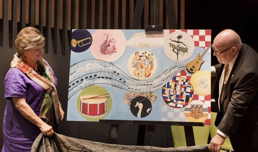 Harmonievoorzitter Joop Bisselink en Corry Dijkstra van de Kunstcommissie onthullen het kunstwerk.