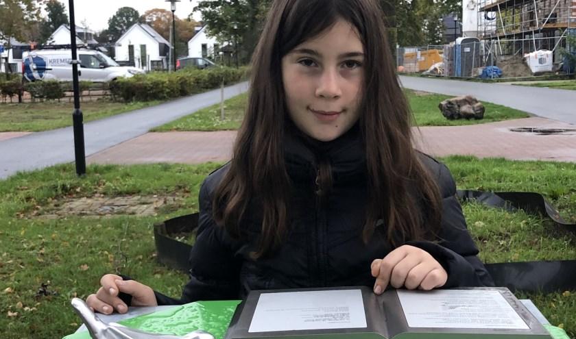 Bij de gedichtentafel in het Dokter Ruttenpark toont Ilaya trots het boek waarin haar gedicht 'verhuizen' is opgenomen.