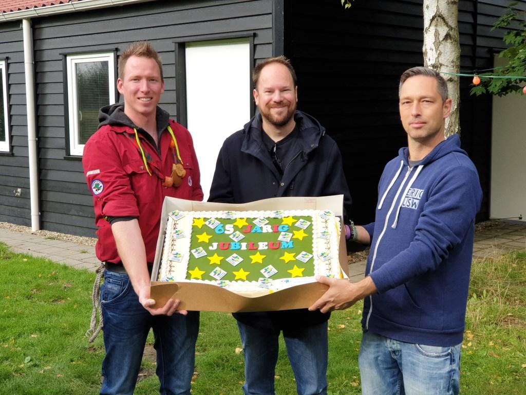 De groepsvoorzitter en penningmeester krijgen de taart overhandigd van Barry Mellegers van de gebiedscommissie. Foto: Scouting Hoogvliet © DPG Media