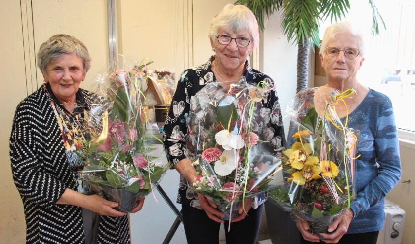 De jubilarissen werden verrast met een mooi bloemstukje. Niet op de foto Jannie van Buren. (Foto:Ria Scholten)