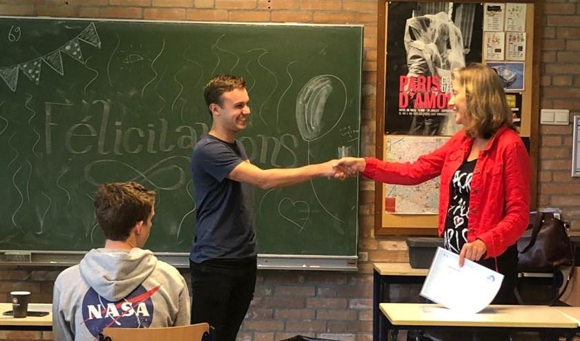 Docent Hermien Hol overhandigt leerling DELF-diploma. (Foto: CSG De Lage Waard)