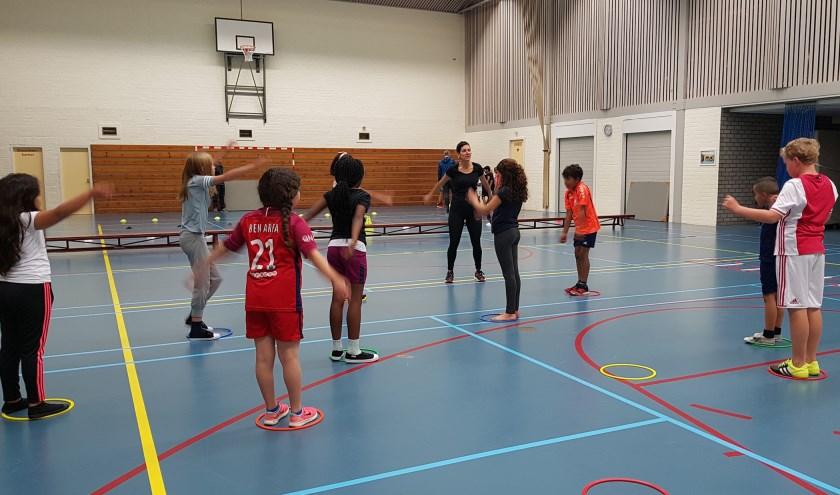 Anoek van der Heijden (Kinderfysiotherapie IJsselstein) geeft hardloop aanwijzingen aan enthousiaste leerlingen.