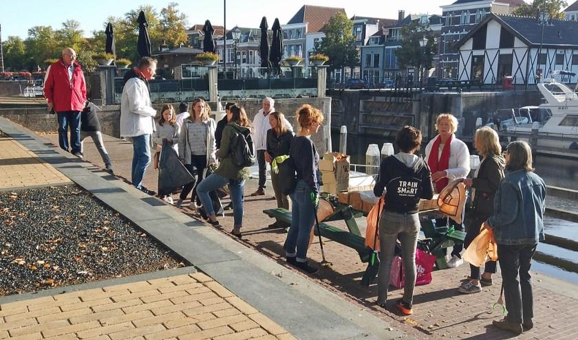 Vrijwilligers verzamelen bij de picknicktafel in de Lingehaven waar grijpers en afvalzakken worden uitgedeeld. Beeld uit film Gorkumsnieuws.nl)