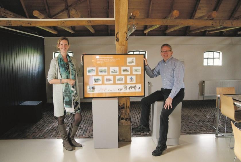 Angela en Tom Kemperman, kinderen van Harrie Kemperman, met een collage die tijdens de expositie wordt getoond.