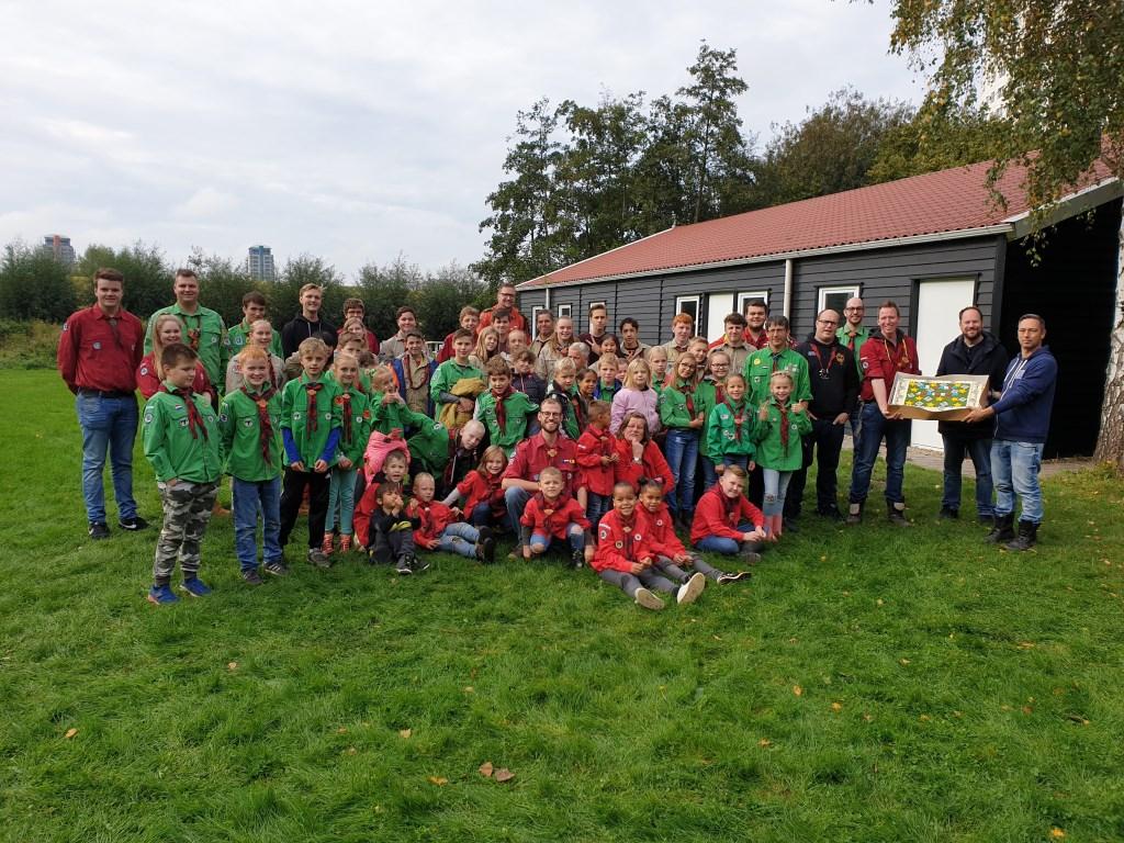 De leden van Scouting Hoogvliet voor hun clubhuis met de overhandigde taart. Foto: Scouting Hoogvliet © DPG Media