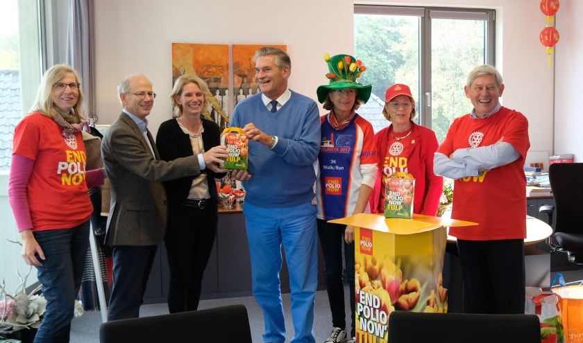Carole Wishaupt, Joost Sanders en leden van Rotary Zeist bieden burgemeester Frits Naafs bloembollen aan.