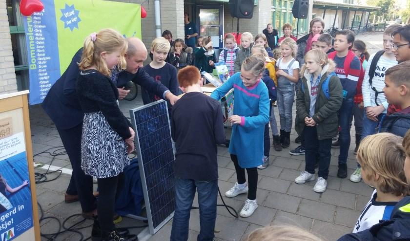 Leerlingen van Openbare Basisschool De Bogerd onthullen een zonnepaneel en met de wethouder steken ze de stekker in het Zonnedakproject.