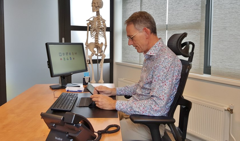 """Huisarts Hans Bruggeman aan het inbellen in zijn praktijk: """"Als huisarts overzie je de totale situatie van de patiënt, ook het sociale domein."""""""