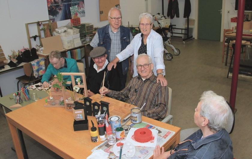 Wendy de Haan, coördinator van Rode Kruis Welfare Duiven, samen met andere vrijwilligers en ouderen die spullen maken voor de verkoopdag.