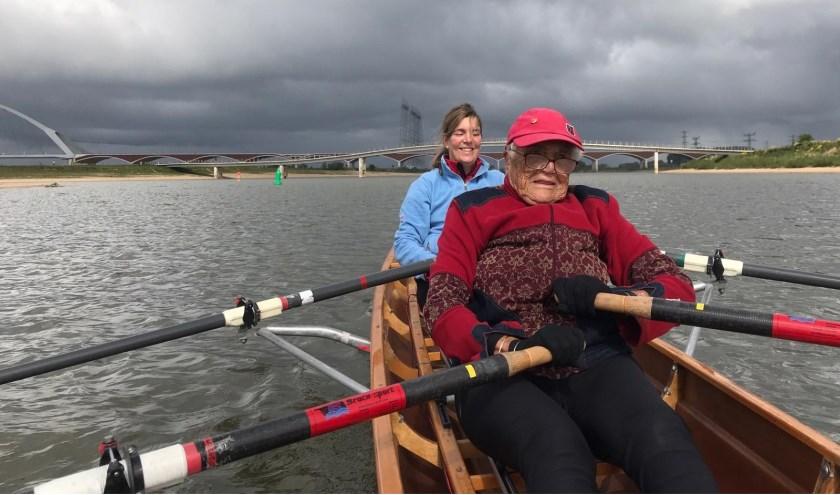 Wereldrecordhoudster 2 km indoor Marijke van den Berg (91) roeit met de ruim 45 jaar jongere Astrid van der Looij op de Spiegelwaal bij Nijmegen.