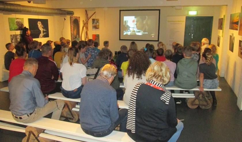 De kinderen kijken naar de video van Wereld Natuur Fonds.