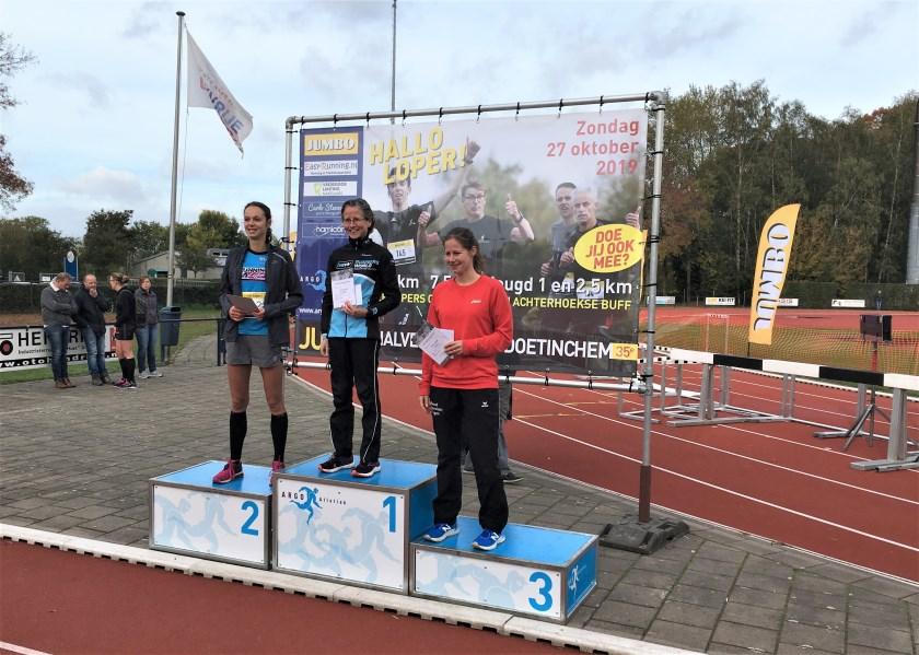 Mireille Baart staat op de hoogste trede van het podium nadat zij de Halve Marathon van Doetinchem had gewonnen.