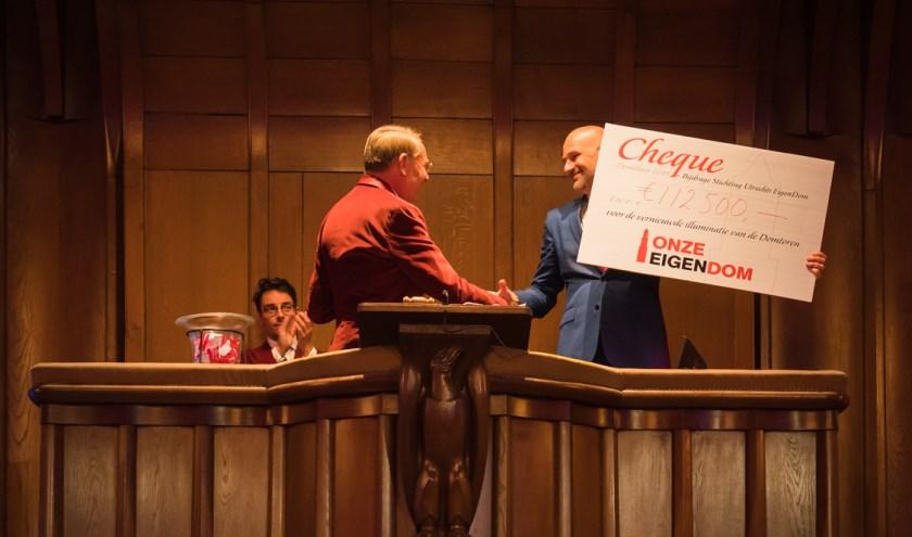 Voorzitter Olav Rosenberg van de Stichting Utrechts EigenDom (links) overhandigt een cheque aan wethouder Victor Everhardt.