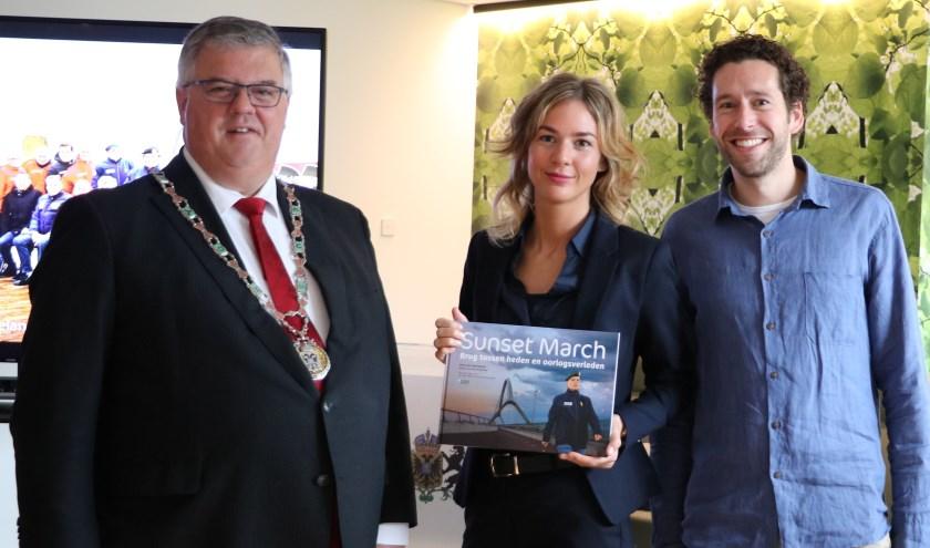 Jaleesa Derksen en Joris Jan Voermans bieden het eerste exemplaar van het boek 'Sunset March - Brug tussen heden en oorlogsverleden' aan burgemeester Hubert Bruls aan.
