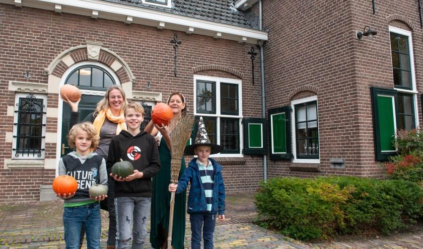 Diana van Sloten (links) en Anne Nyst vertellen over de aanstaande Pompoen Potter Party. Ook op de foto; Diana's drie zonen Tijn, Jord en Mees.