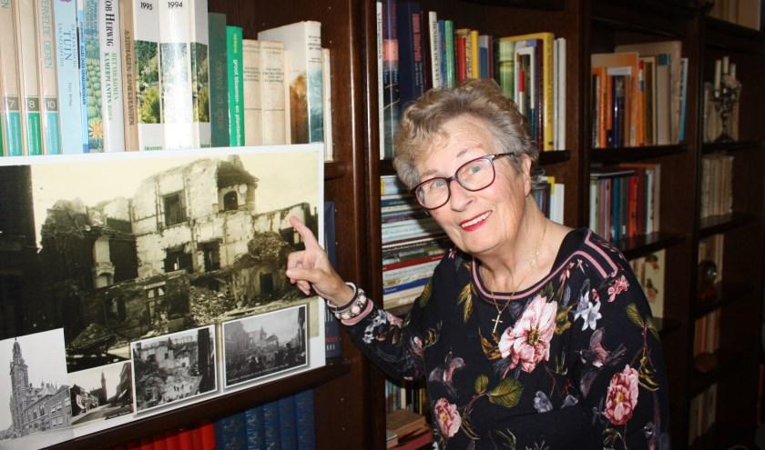 Schrijfster Geke van de Merwe wijst naar een foto die daags na de Stadhuisramp in Heusden is gemaakt. Bij deze 'oorlogsmisdaad' van de Duitsers verloren 134 onschuldige kinderen en volwassenen het leven.