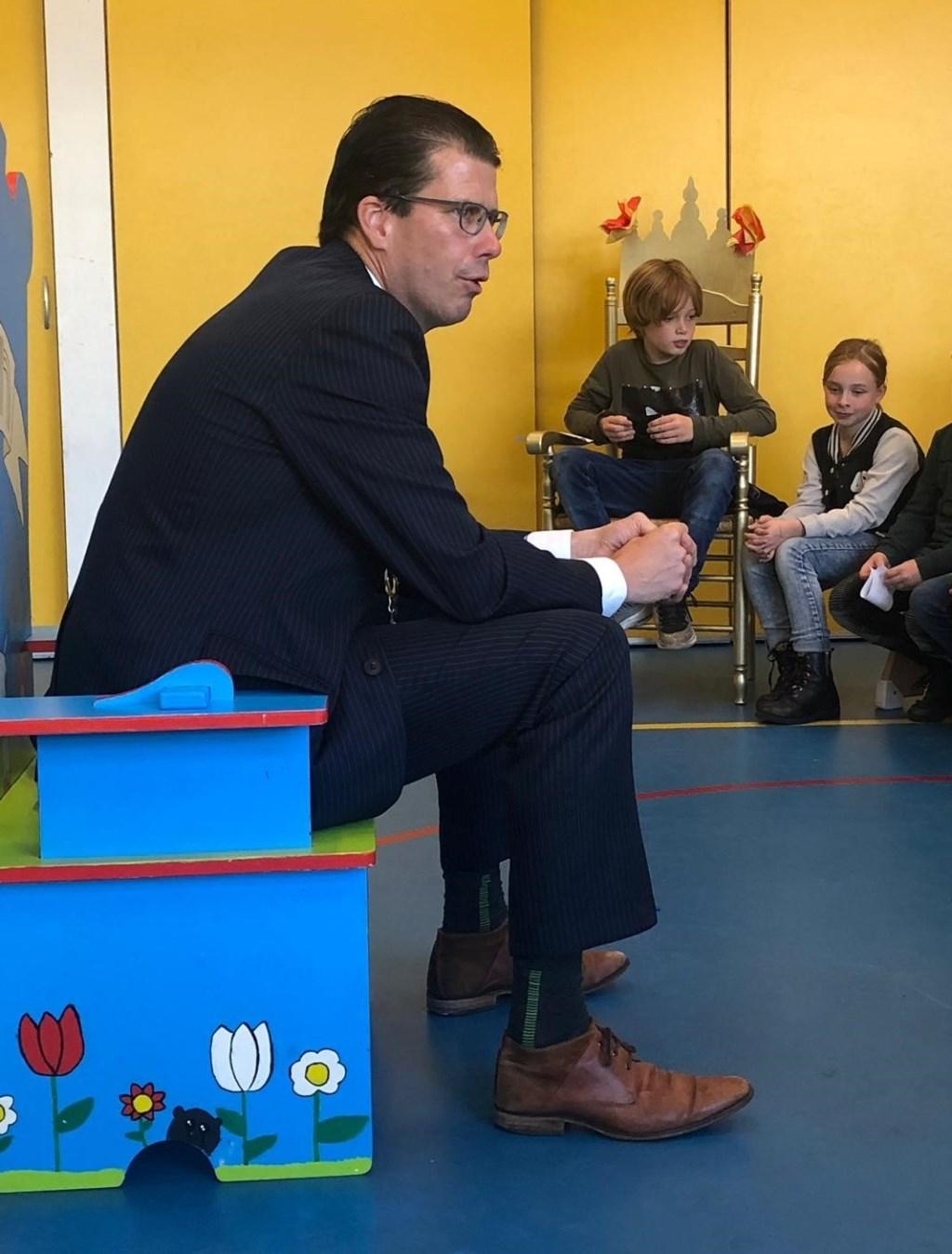Burgemeester Joost van Oostrum vertelt met plezier over zijn werk op obs Menno ter Braak. In het midden leerling Gijs.