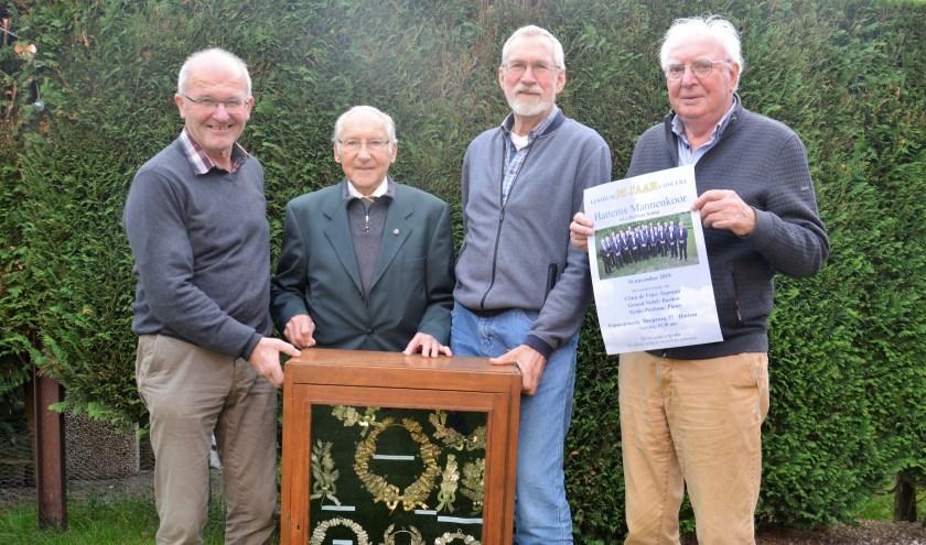 Jan de Groot, Karl Veneman, Wieger van der Veen en Gerrit Hoogers met de kast vol prijzen die het Hattems Mannenkoor afgelopen 95 jaar heeft gewonnen. Foto: Angela van Erven