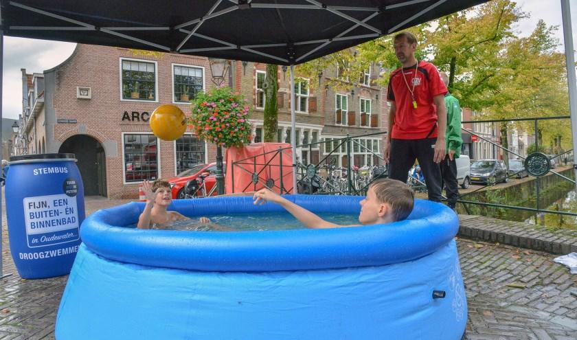 """De eerste ludieke actie van de Oudewaterse Zwem Vereniging (OZV) voor een binnen- en buitenbad in Oudewater. """"Droog Zwemmen"""" op de Markt. (Foto: Paul van den Dungen)"""