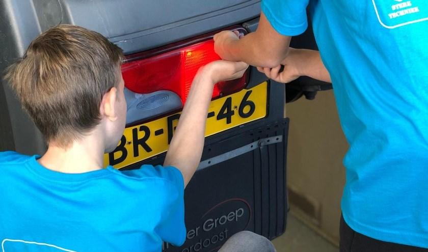Twee leerlingen bekijken de motor van een vrachtwagen bij het bedrijf Truck & Trailer
