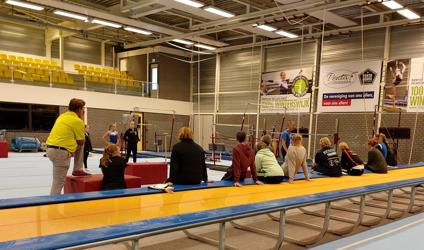 Turntrainers en trainsters volgen bijscholing turnen dames in turnhal.