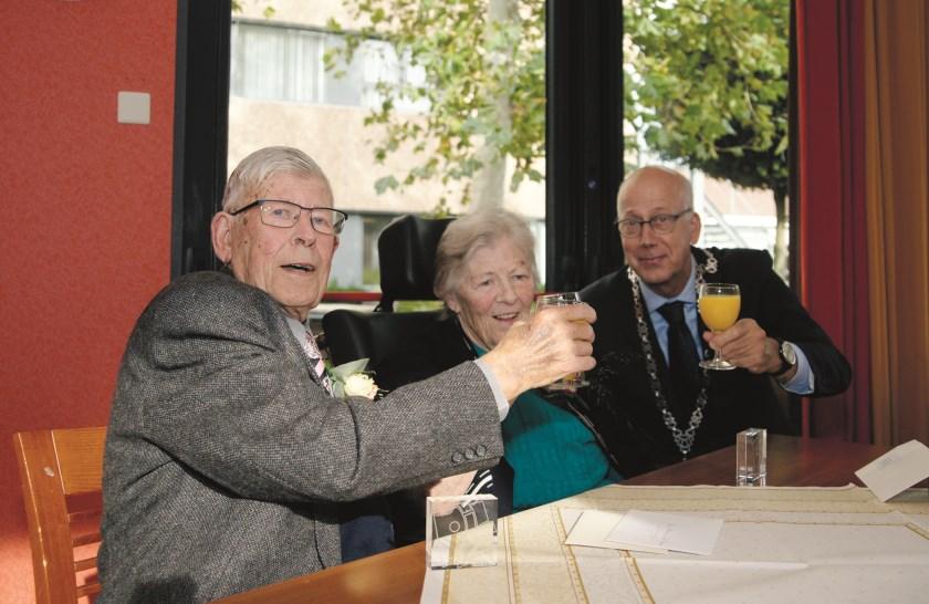Willy en Willy Polman proosten met burgemeester Arend van Hout op hun diamanten huwelijksfeest.