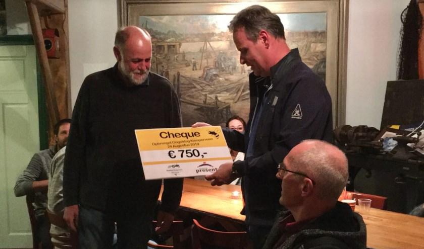 Aalt van den Hul (l.) reikt desymbolische cheque van 750 euro uitaan Wim Junte. (eigen foto)