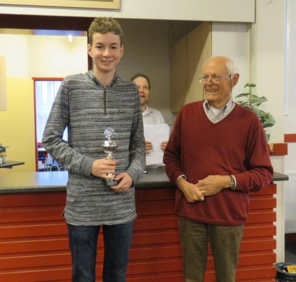 De boomlange Thijs van Dam ontving van jeugdleider Jan Wouters zijn prijs. Op de achtergrond kijkt medeorganisator Hotze Tette Hofstra toe.  © DPG Media