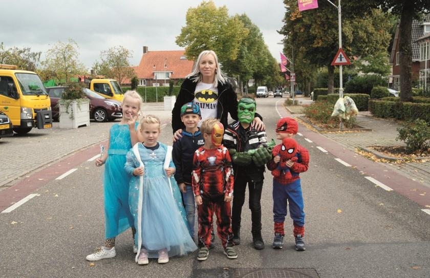 Debbie Veldink van de Stichting Kermis Westervoort met enkele kinderen die zich voor de foto hebben verkleed als prinsessen en superhelden.