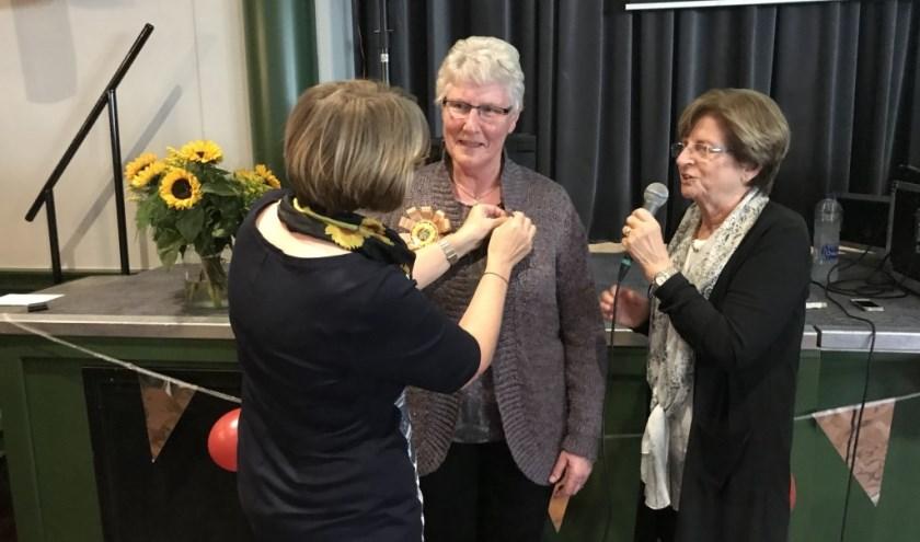 Onder toeziend oog van Marianne Blaauwhof wordt door voorzitter Conny Piels het insigne bij Truus Peters opgespeld.