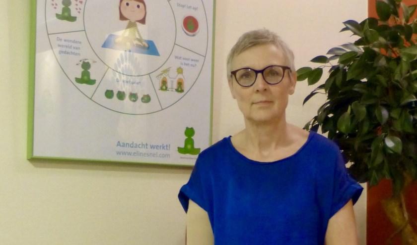 Karin Schellekens in haar praktijkruimte, waar ze onder andere de trainingen 'Mindful opvoeden' en 'Aandacht werkt!' geeft.