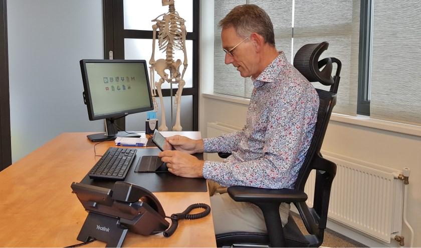 """Huisarts Hans Bruggeman aan het inbellen in zijn praktijk: """"Als huisarts overzie je de totale situatie van de patiënt, ook het sociale domein."""" (Foto: PR)"""