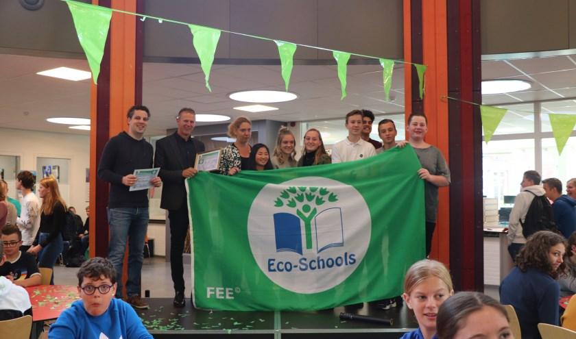 Trots tonen de leerlingen van de ECO-raad de vlag aan hun medeleerlingen.
