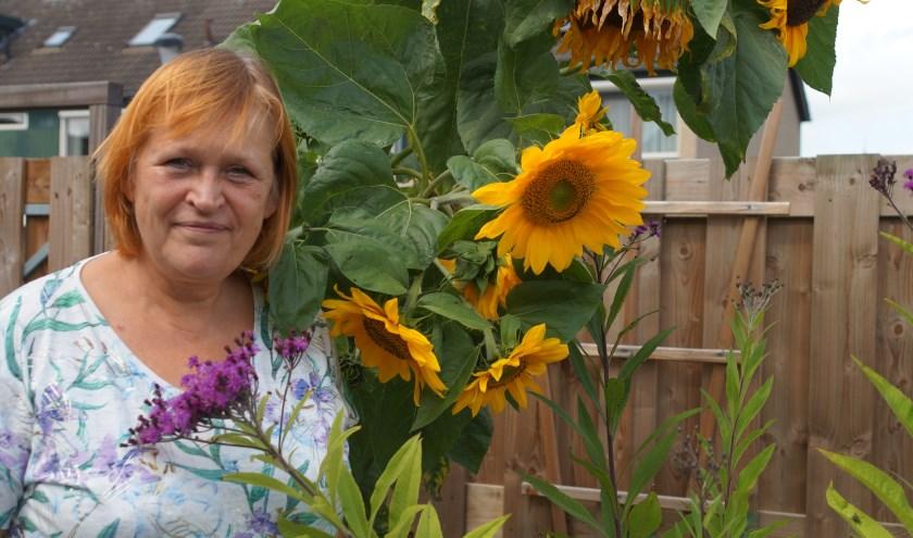 """Marguerite Boersma houdt van tuinieren, is blij met de flinke zonnebloemen in haar tuin. """"Na het ophogen van de wijk is het hier een stuk minder groen geworden."""""""