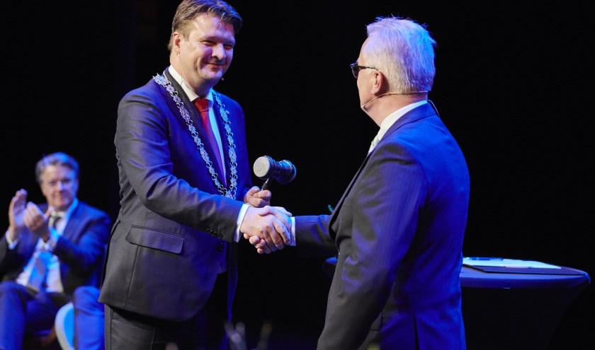 Plaatsvervangend raadsvoorzitter Cor Gabriëls draagt de ambtsketen en voorzittershamer aan Han van Midden over. [Foto: gemeente Roosendaal / Timo Reisiger]