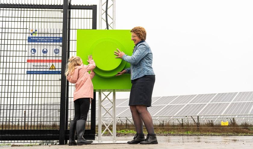 Lois Goossen en wethouder Van Abbema hebben de stekker in het stopcontact gestoken. Het zonnepark is open. Foto: Jimmy Musters