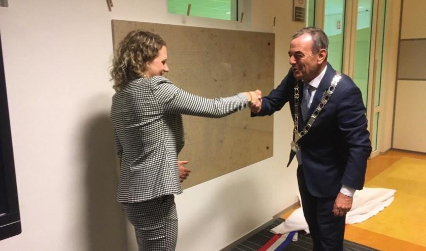 De burgemeester en de voorzitter van de leerlingenraad onthullen samen de plaquette.