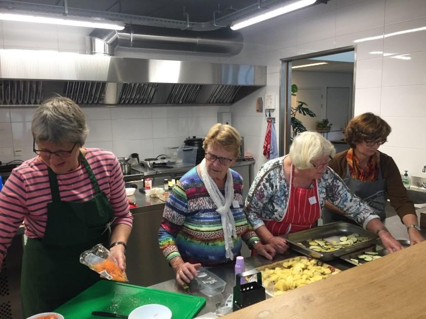 Vrijwilligers druk bezig met de voorbereiding van de maaltijd. Foto: Giny Molenkamp