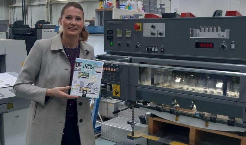 Franca de Winter bij de drukpers van Zoeteweij toen de eerste vellen van het Leuk Zeeuwse Kookboek werden gedrukt. FOTO: Margee Schroevers