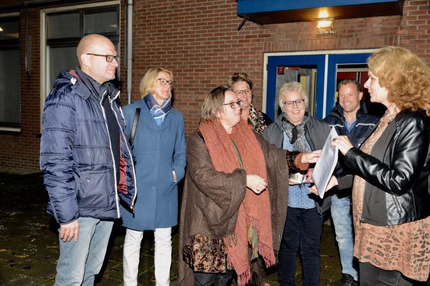 Op het speelterrein bij de oude school krijgt wethouder Hartman van Bertie van Gelderen de uitslag van het onderzoek overhandigd.