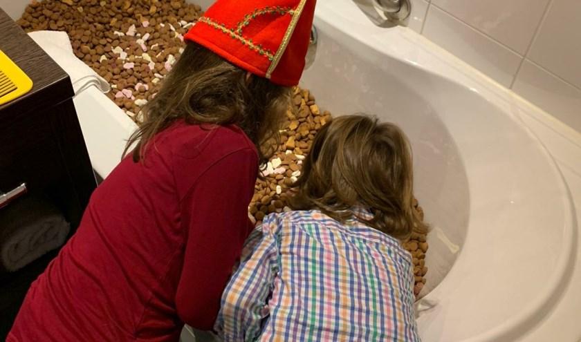 Kinderen verbazen zich over het bad vol pepernoten