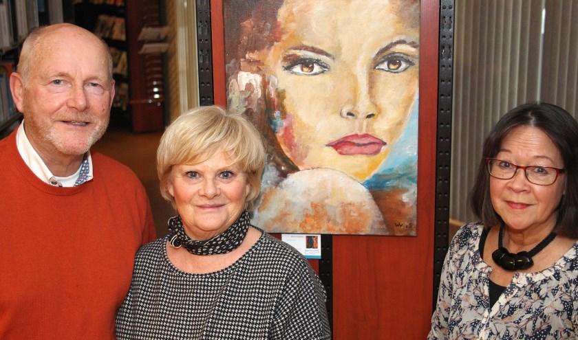 Marina en Willem Vreugdenhil (l) en Shirley Bijholt bij een portret met sprekende ogen van Willem. (foto: Koos Romeijn)