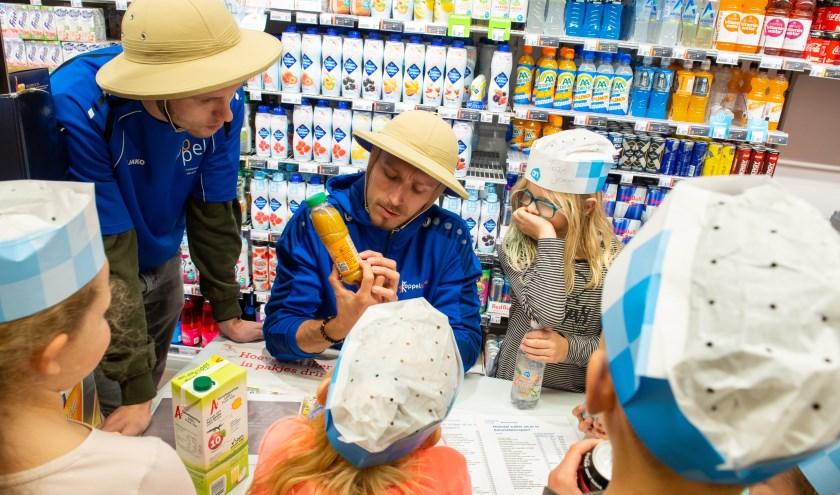 Jeroen de Lange van Heel Epe Beweegt legt kinderen van de Jenaplanschool uit hoeveel suiker er in dit drankje zit. Naast hem staat stagiair Roel.