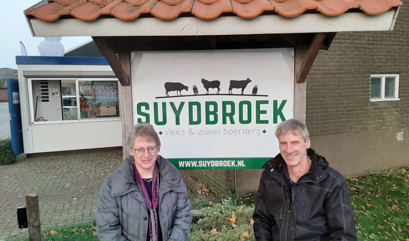 Marisca en John voor het naambord van hun boerderij. Op de achtergrond de unit met daarin de melktap en de vleeskoeling.