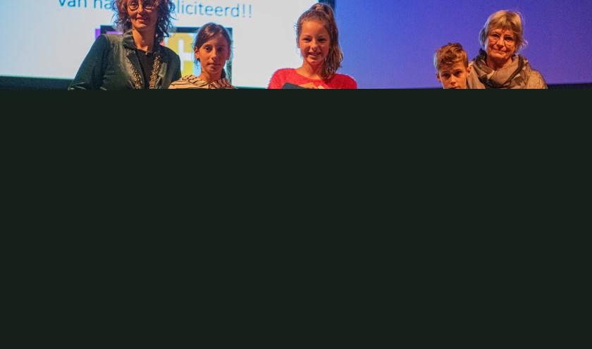 De drie mooiste tekeningen uit de gemeente Oirschot, met in het midden winnares Annamarie Boer.
